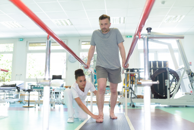 physical therapist assisting man on walking