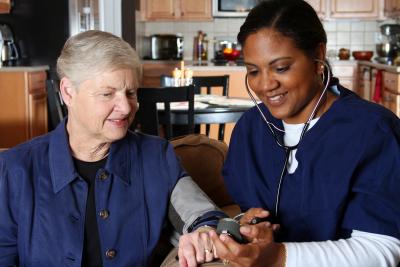 nurse checking blood pressure of a senior