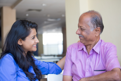 caregiver and senior smiling each other