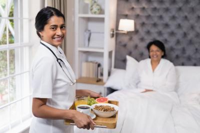 nurse serving food to a senior